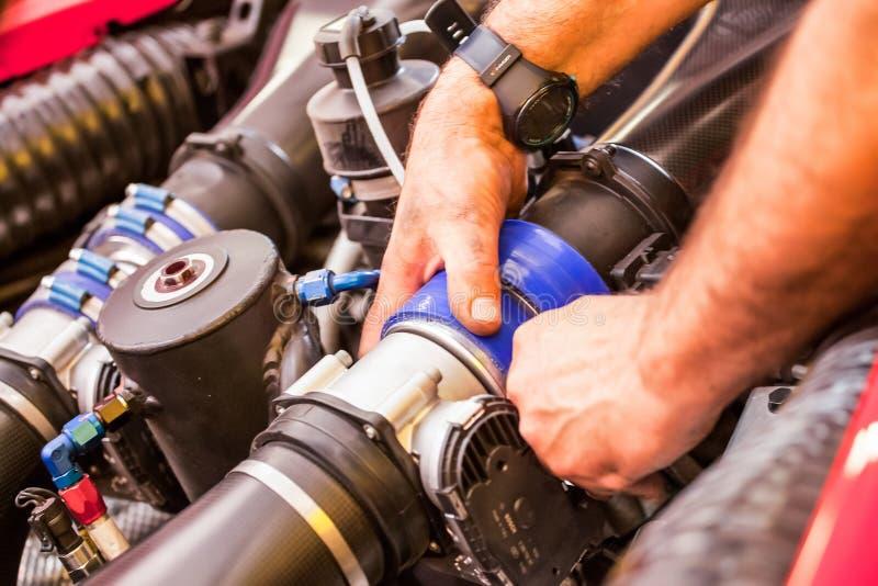 En mekaniker ?r granska och reparera motorn och n?gra mekaniska delar av en supercar arkivbild
