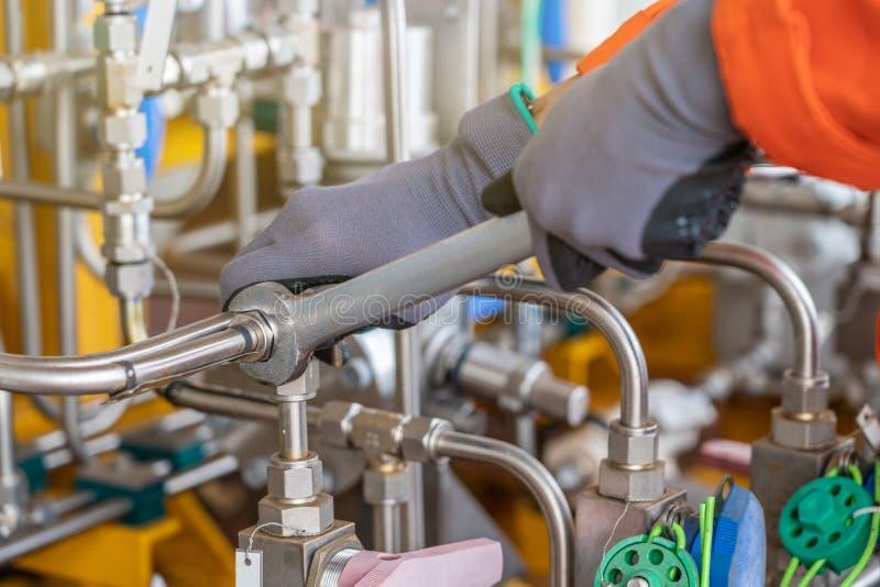 En mekanikeroperatörsknipa och att dra åt rostfritt stålrörsystemet, genom att använda kombinationsskiftnyckeln royaltyfri foto