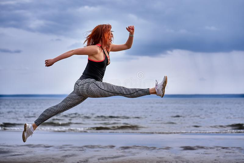 En mellersta åldrig kvinna med röda hårhopp, medan jogga fotografering för bildbyråer