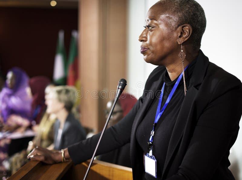 En mellersta kvinna för afrikansk nedstigning som talar in i en mikrofon royaltyfria foton