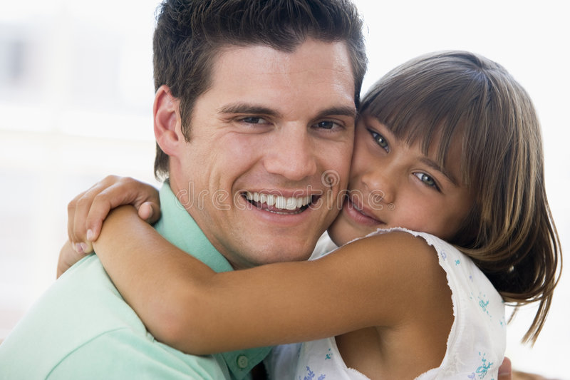 En mens en jong meisje die koesteren glimlachen royalty-vrije stock fotografie