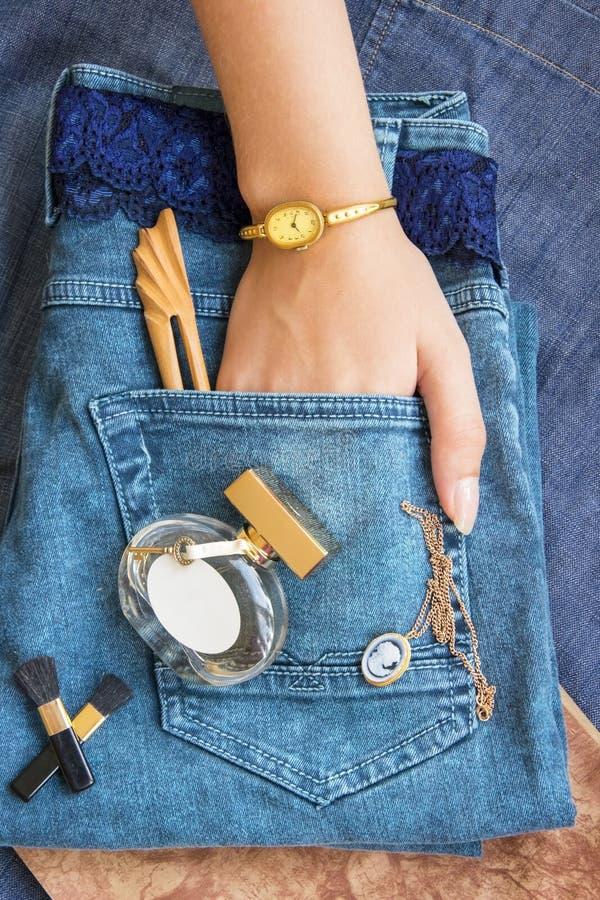 En mentira de los tejanos una botella de perfume, un reloj afiligranado del trabajo del oro, imagen de archivo