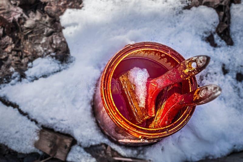 En metallisk ask med målarfärg och två borstar i snön royaltyfri bild
