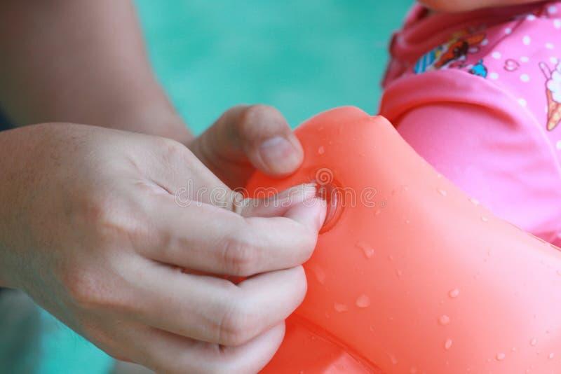 En mettant le bras d'anneau de natation flottez pour l'enfant, avec la lumière du jour photos libres de droits