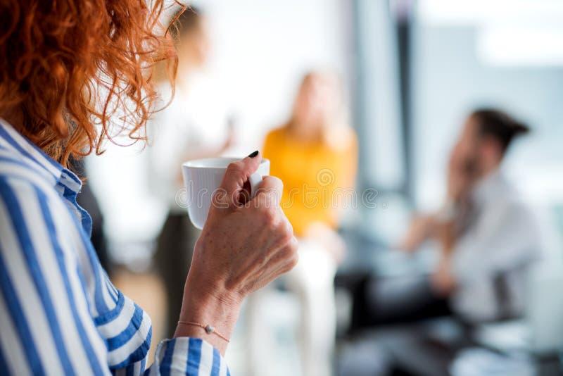En midsection av affärskvinnan i ett kontor som rymmer en kopp kaffe royaltyfri foto