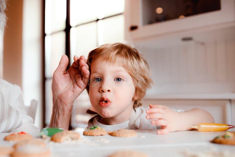 En midsection av den höga farmodern med den lilla litet barnpojken som hemma gör kakor royaltyfri bild