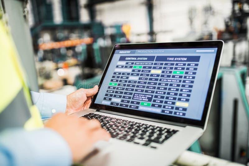 En midsection av en industriell mantekniker med bärbara datorn i en fabrik som arbetar arkivbild