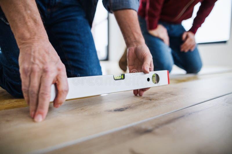 En midsection av mannen med hans fader som lägger vinyldurken, ett nytt hem- begrepp fotografering för bildbyråer