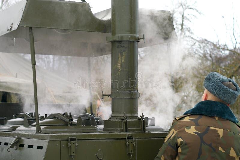 En militär kock förbereder matställen för soldaterna i vinter marschera metallkök med bränsleträ fotografering för bildbyråer