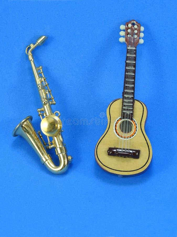 En miniatyrgitarr och saxofon på blå bakgrund royaltyfri foto