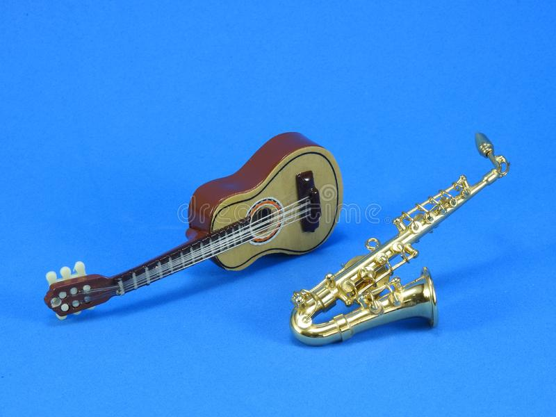 En miniatyrgitarr och saxofon p? bl? bakgrund royaltyfria foton