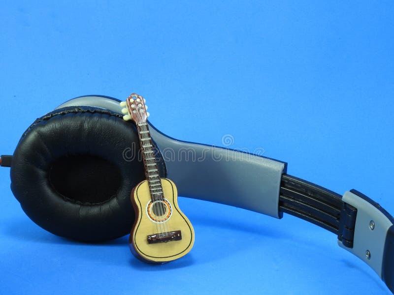 En miniatyrgitarr propped upp p? en svart- och silverheadphone arkivfoto
