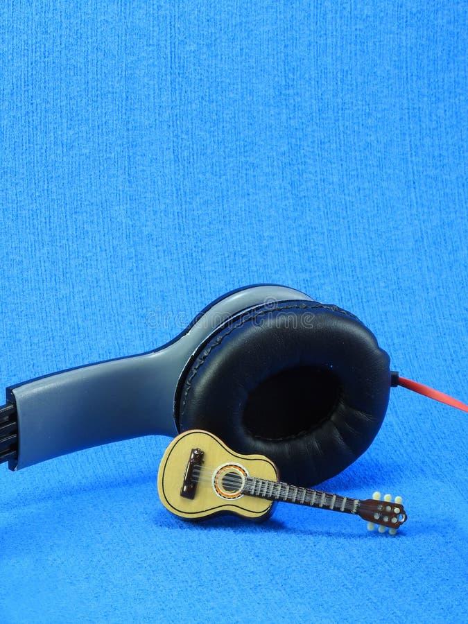 En miniatyrgitarr propped upp p? en svart- och silverheadphone royaltyfria bilder
