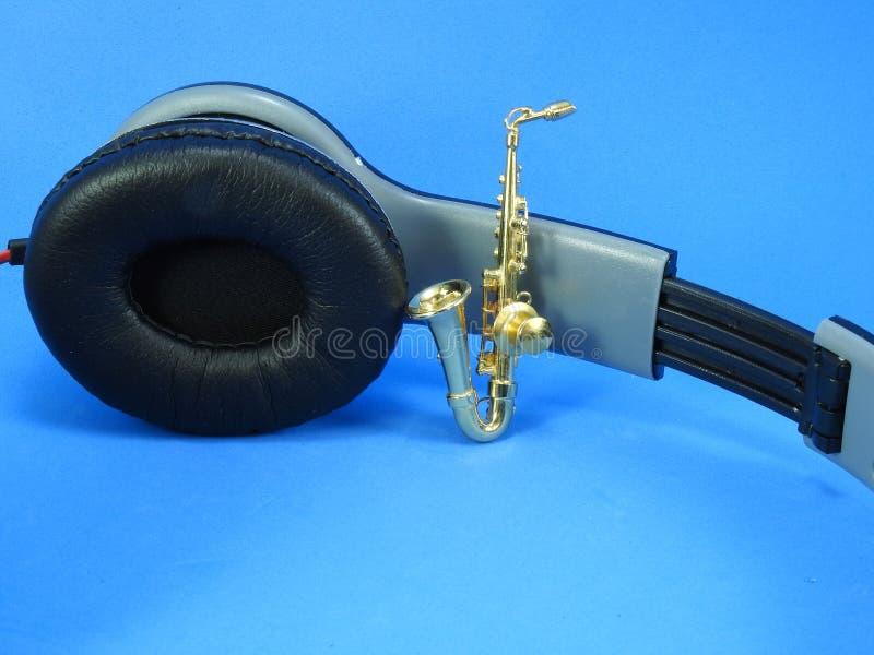 En miniatyrguld- saxofon propped upp på en svart- och silverheadphone royaltyfria foton