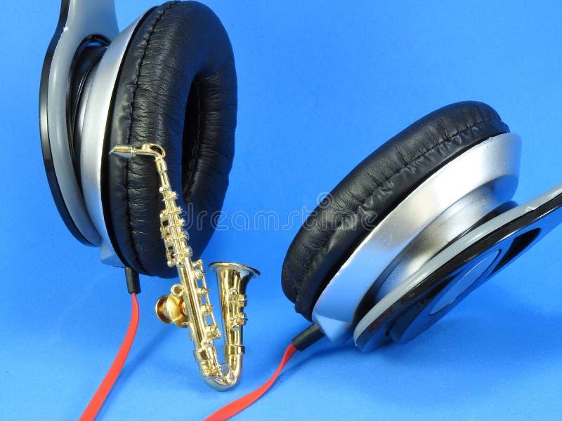 En miniatyrguld- saxofon propped upp p? en svart- och silverheadphone fotografering för bildbyråer