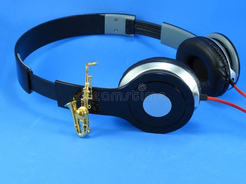 En miniatyrguld- saxofon propped upp p? en svart- och silverheadphone royaltyfri fotografi