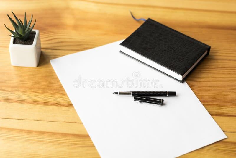 En minimalist arbetsplats med en anteckningsbok, ett ark av papper, en penna på en trätabell royaltyfria bilder