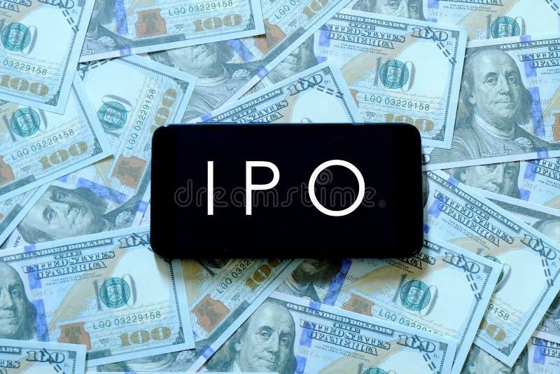 En mobiltelefon med bokstaven IPO på skärmen på räkningar eller sedlar för en dollar IPO står för initialt offentligt erbjuda arkivbild
