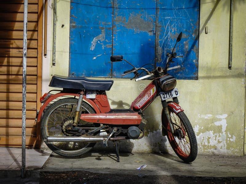 En Mobylette parkering på gatan arkivbilder