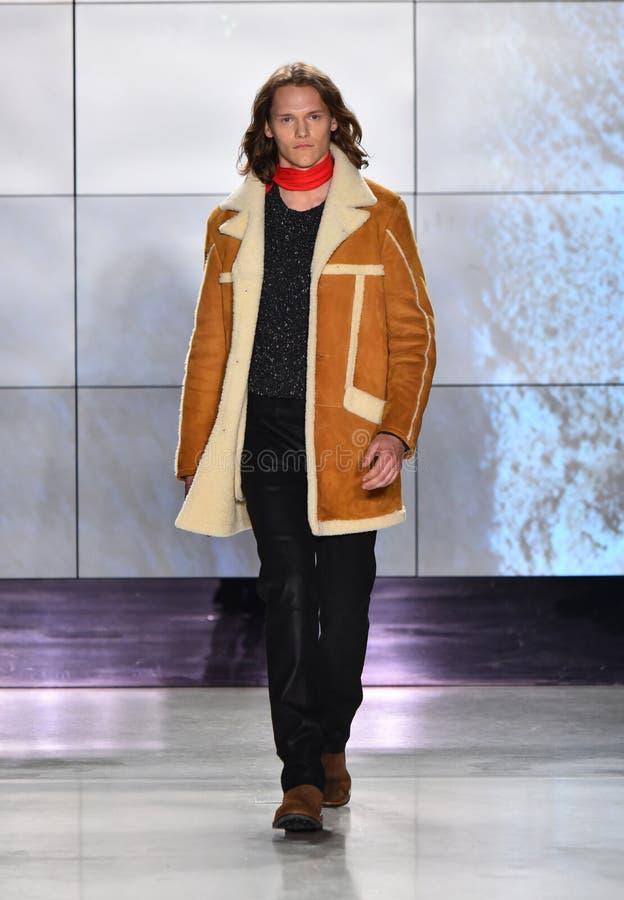 En modell bär en dräkt på landningsbanan på den Deveaux modepresentationen royaltyfri bild