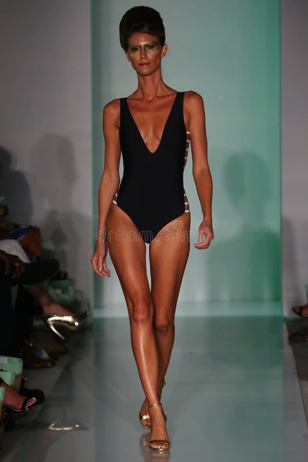 En modell går landningsbanan i formgivarebaddräkt på den Mia Marcelle modepresentationen royaltyfri bild