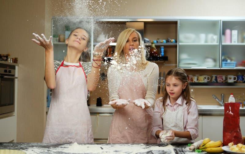 En moder med hennes två ungar som har gyckel i köket arkivfoton