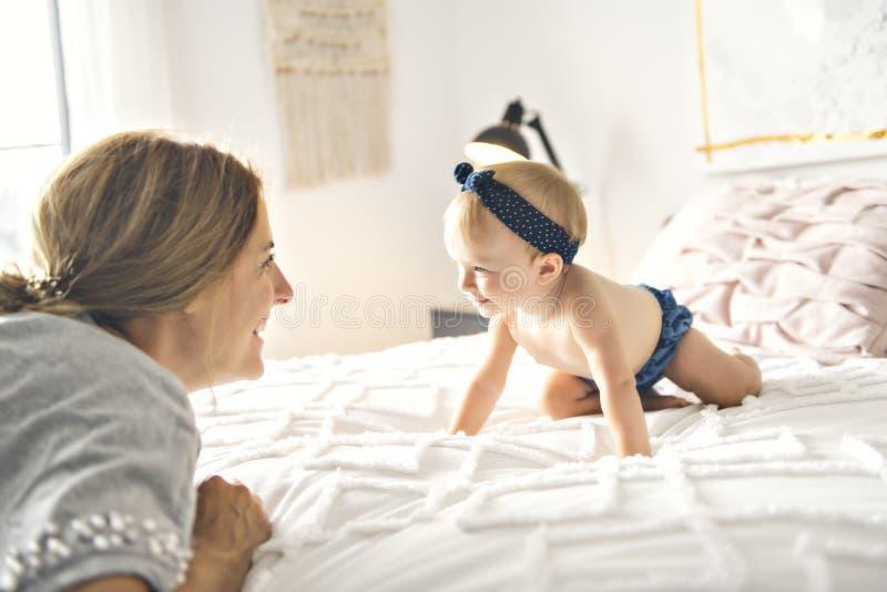 En moder och behandla som ett barn flickan på säng royaltyfria bilder