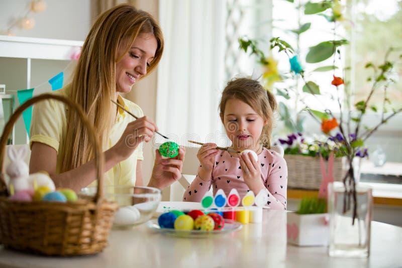 En moder och en dotter som firar påsken som målar ägg med borsten royaltyfria bilder