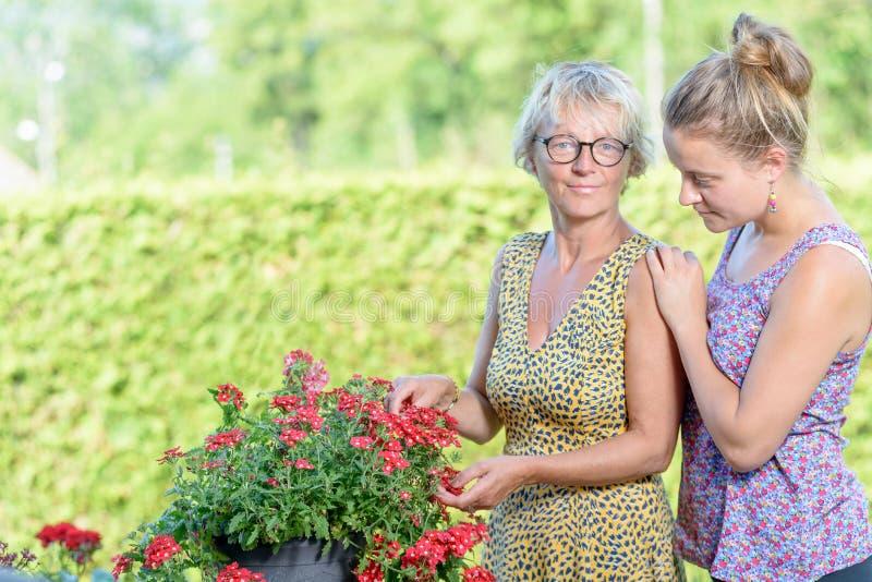 En moder och en dotter som att bry sig för blommor royaltyfri foto