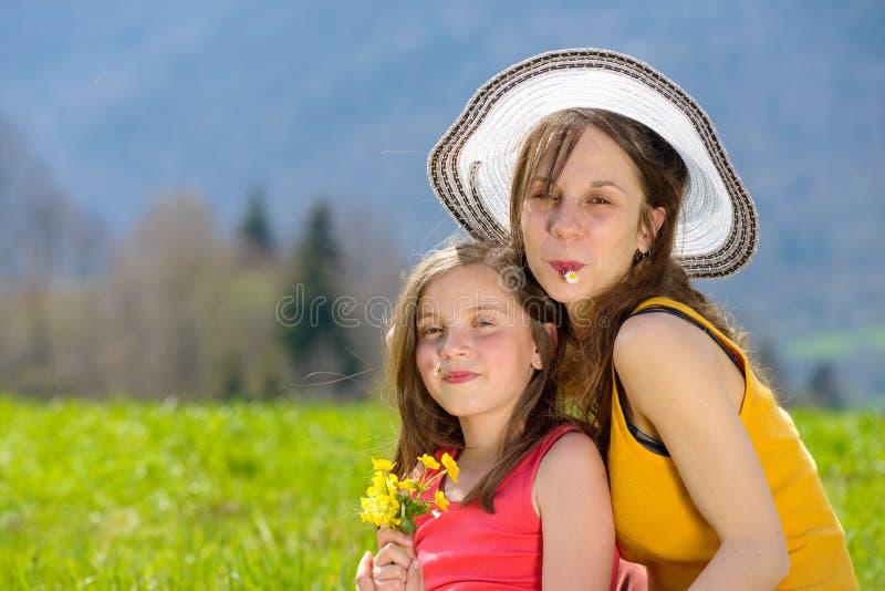 En moder och hennes dotter med en blomma i hans mun arkivbild