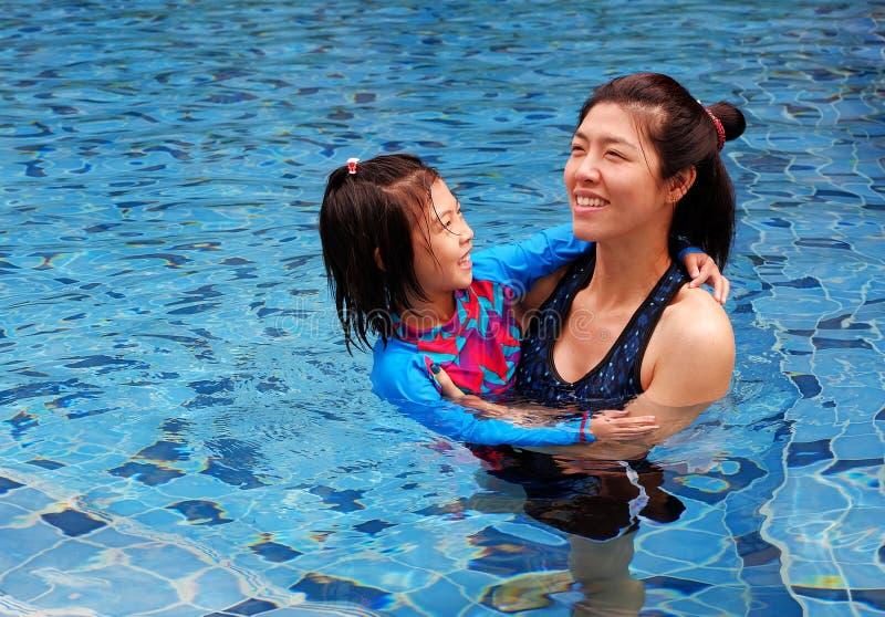 En moder som undervisar hennes dotter att simma royaltyfria bilder