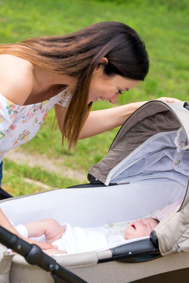 En modercheckin henne att behandla som ett barn i en sittvagn i parkerar royaltyfri foto