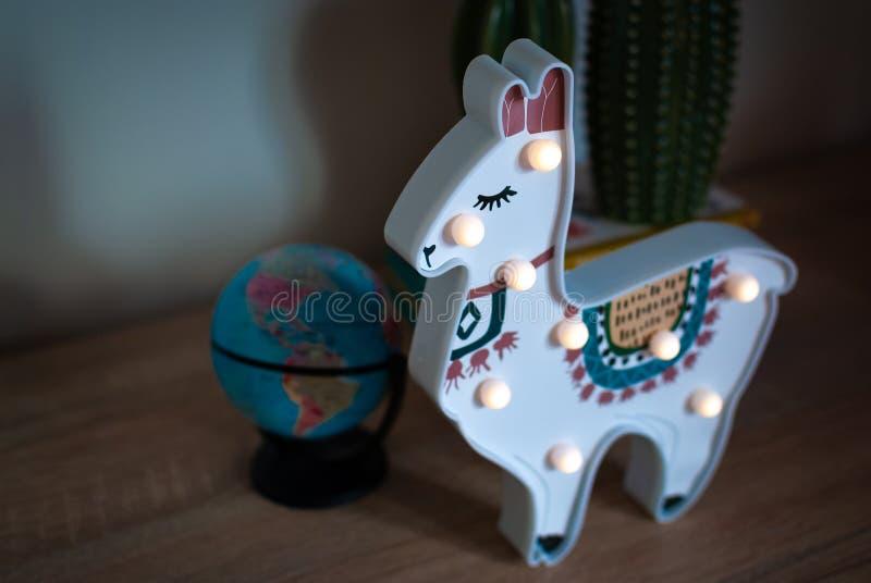 En moderiktig lama lurar nattlampanseende på en sängkant i gryning eller soluppgångljus arkivfoton