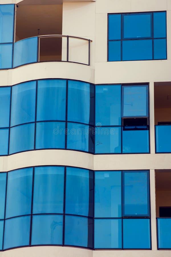 En modern byggnad med bakgrund för exponeringsglasfönster arkivbilder