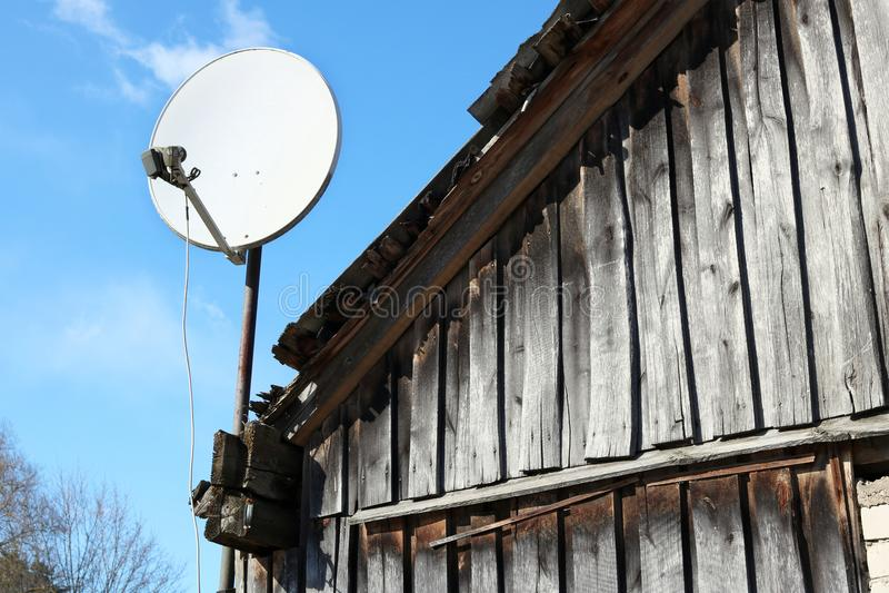 En modern satellit- maträtt fixas på taket arkivfoton
