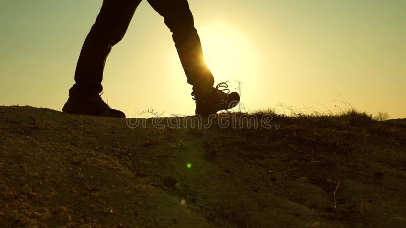 En modig man-handelsresande som klättrar till överkanten av ett berg som promenerar en bana längs en farlig stenig kant brant arkivfoto