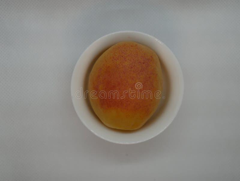 En mogen aprikos i en liten vit porslinplatta på en vit bakgrund Naturligt vitamin sund mat Vegetarisk mat arkivfoton