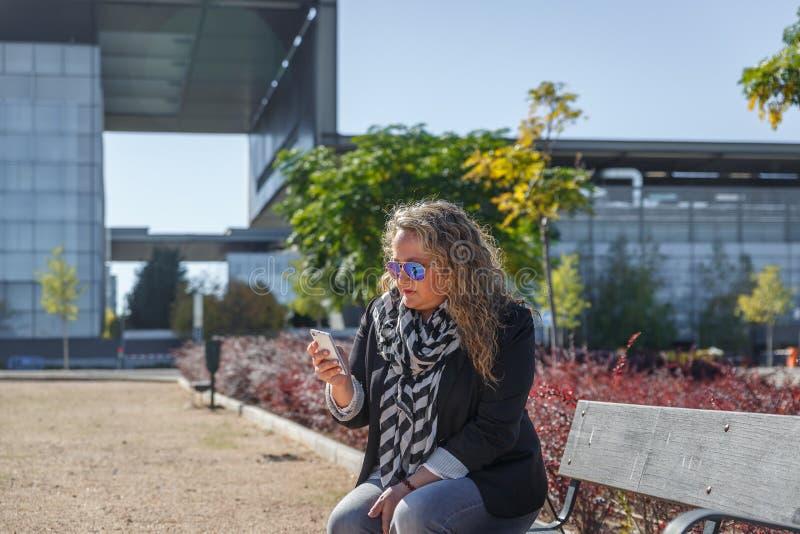 En mogen blond kvinna kontrollerar hennes mobiltelefon, medan sitta på bänken i, parkerar royaltyfri foto