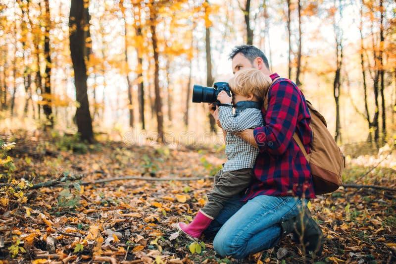 En mogen fader och en litet barnson i en höstskog som tar bilder med en kamera fotografering för bildbyråer