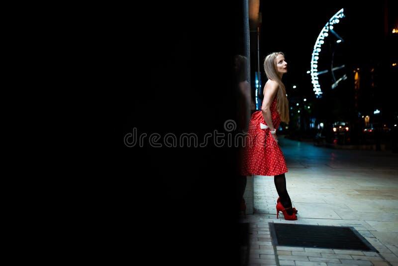 En mogen kvinna i en röd klänning som lutar till väggen på natten fotografering för bildbyråer