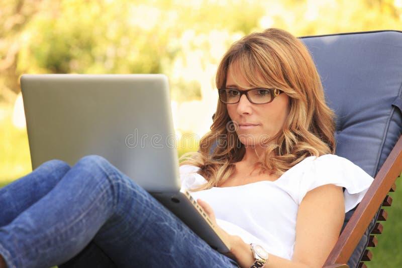 En mogen kvinna som hemma arbetar royaltyfria bilder