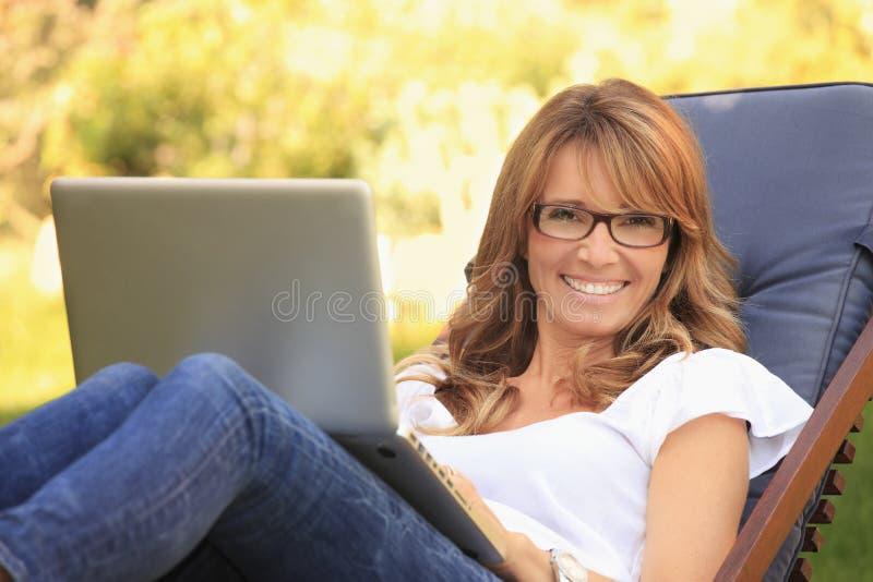 En mogen kvinna som hemma arbetar arkivbilder