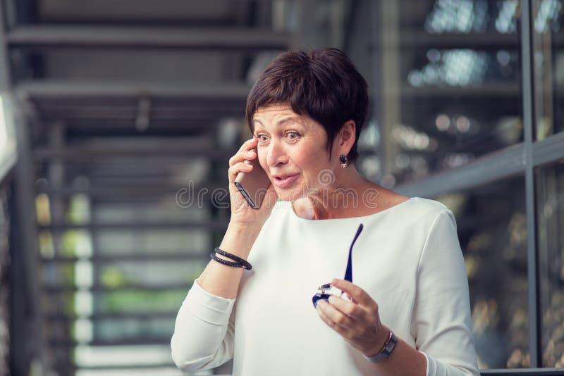 En mogen kvinna som talar på mobiltelefonen som bedövas av vad hon hör arkivfoto