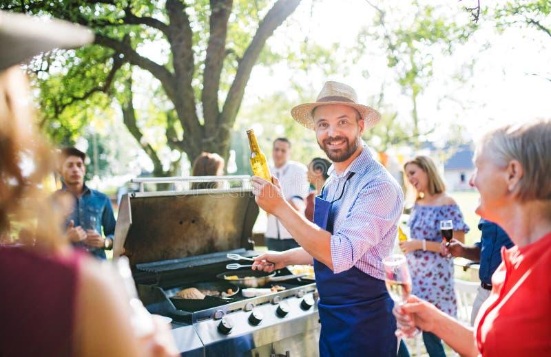 En mogen man med familjen och vänner som lagar mat och tjänar som mat på ett grillfestparti royaltyfria bilder