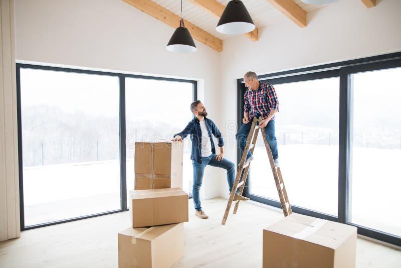 En mogen man med hans höga fader som möblerar det nya huset, ett nytt hem- begrepp royaltyfri fotografi
