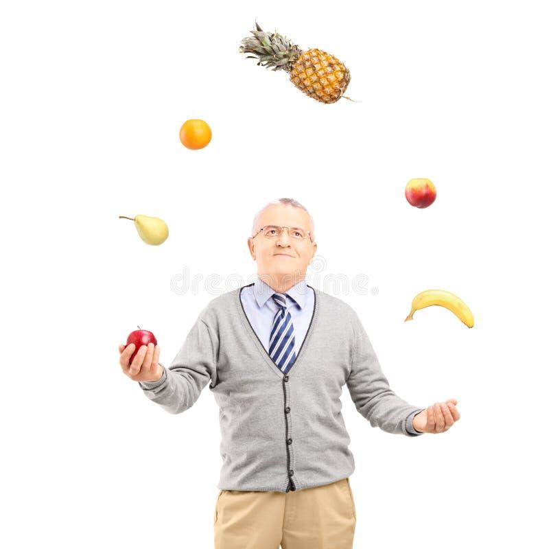 En mogen man som jonglerar frukter royaltyfri bild