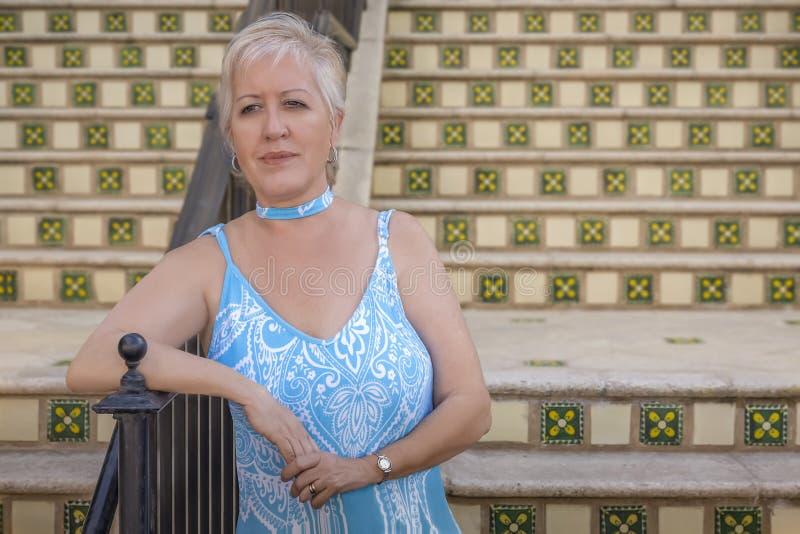 En mogen modern blond kvinna väntar längst ner av momenten som lutar på stången arkivfoto