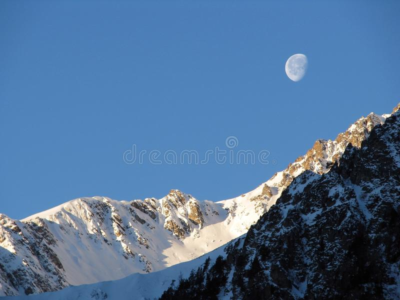 En moon över bergen royaltyfria bilder