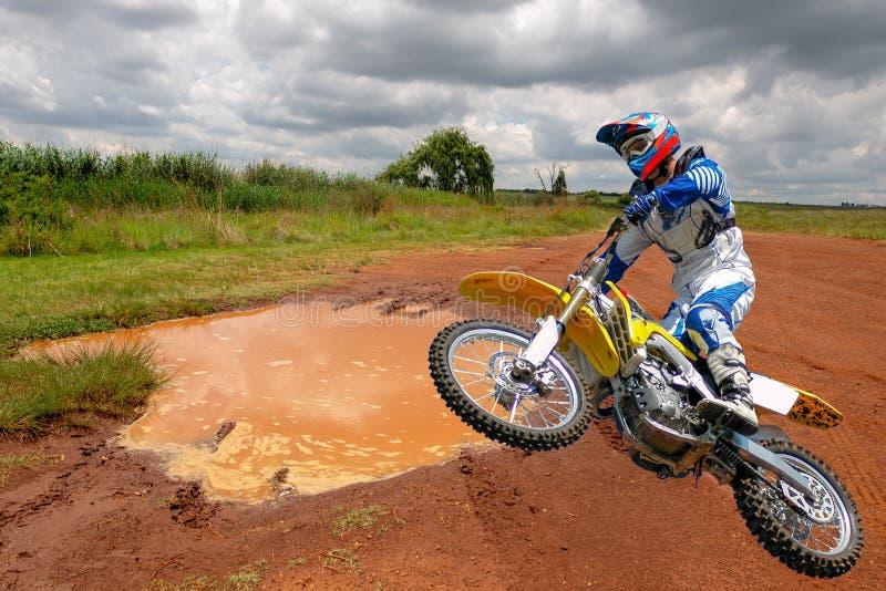 En motocross-racer på en smal väg arkivfoto