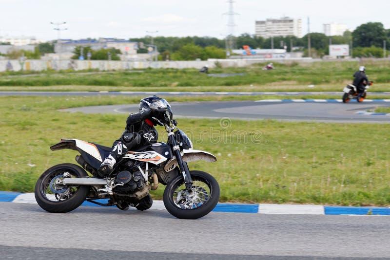 En motorcykeltävlingsförare tar en övning som körs på ett sportspår royaltyfri foto